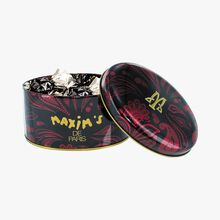 Mini black oval box of dark chocolate hazelnuts. Maxim's